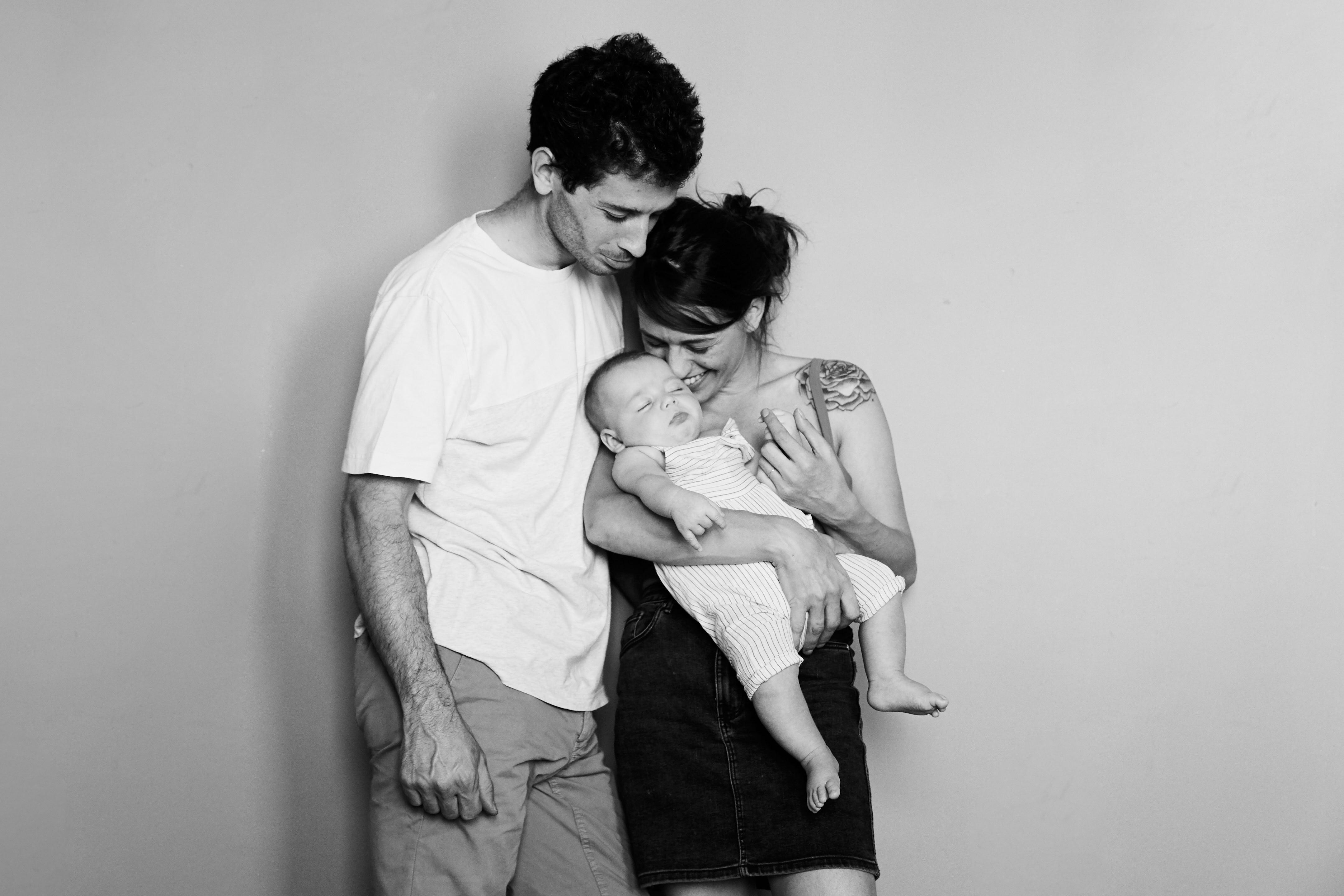 mamma e papà abbracciano figlio neonato