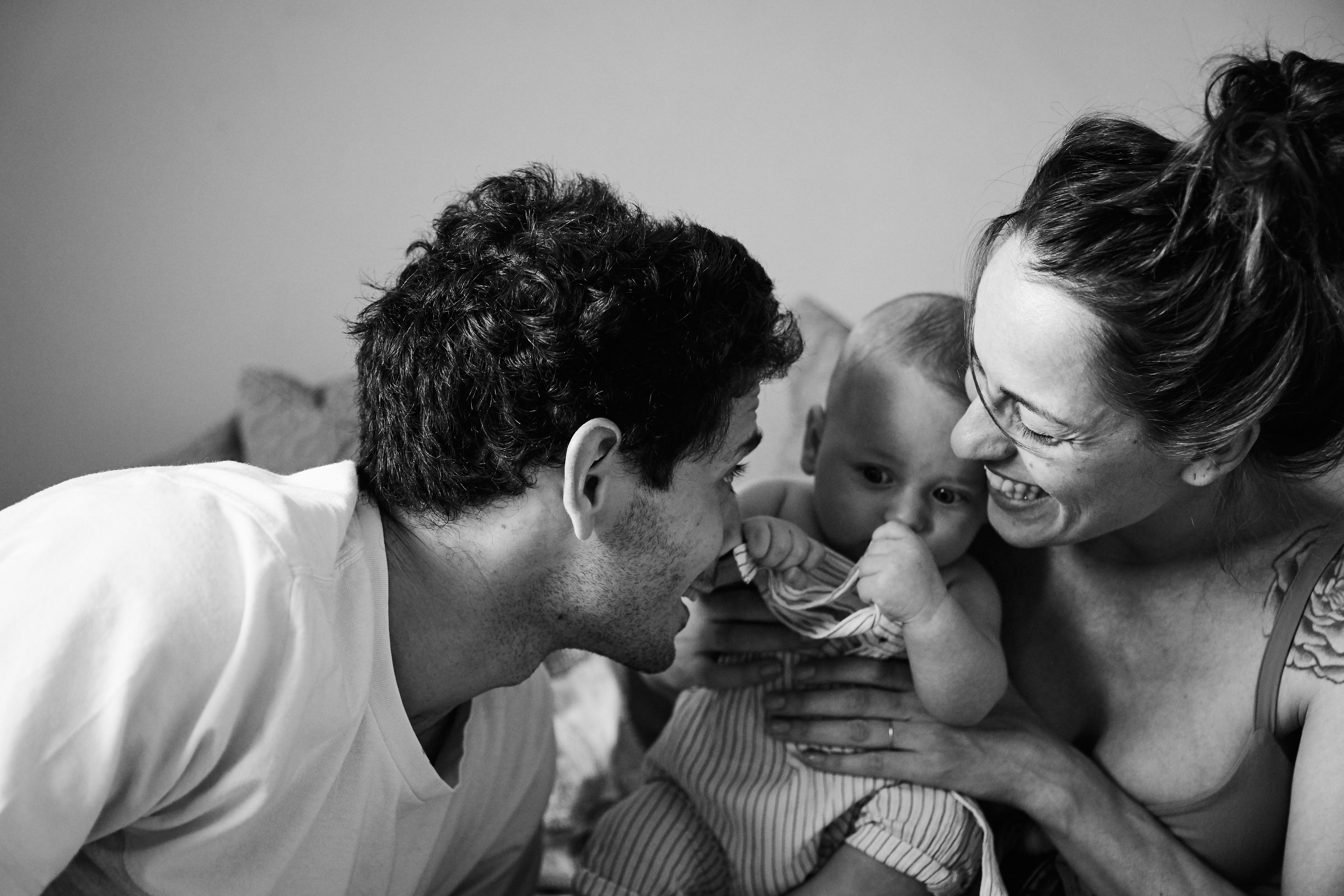 mamma e papà ridono e sorridono con figlio neonato