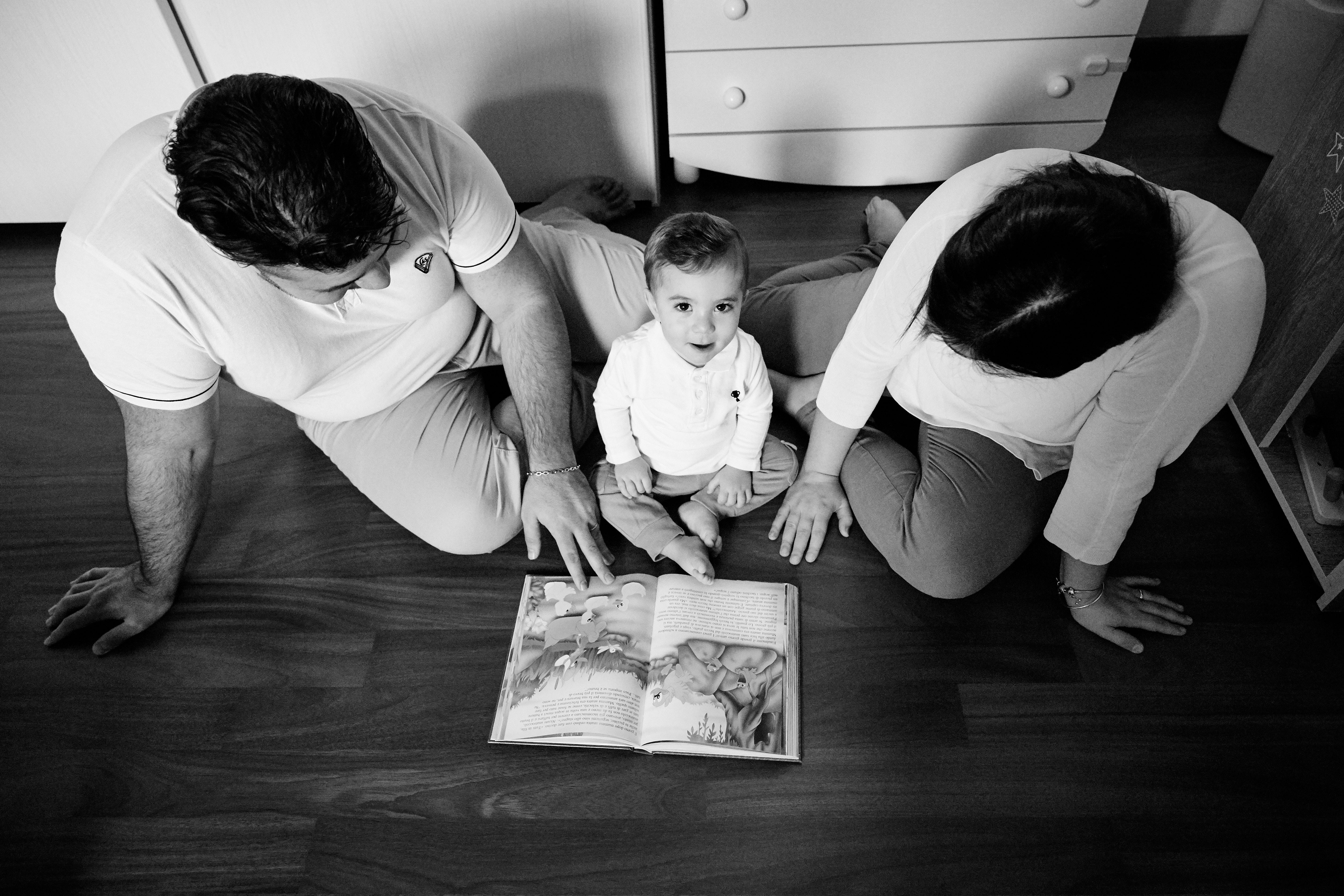 fotografia bambino in bianco e nero con genitori dall'alto