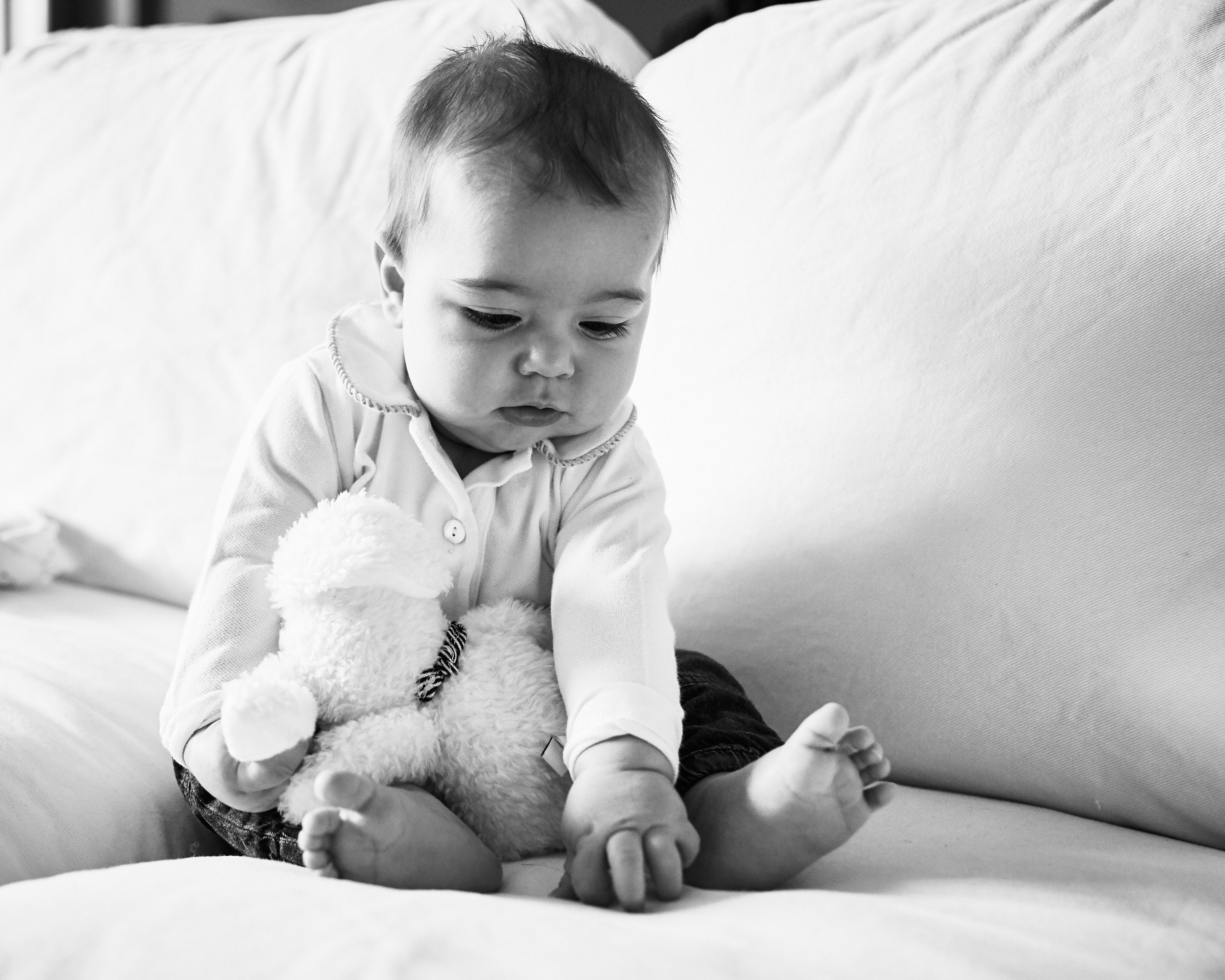 fotografia bambino piccolo in bianco e nero sul divano con peluche