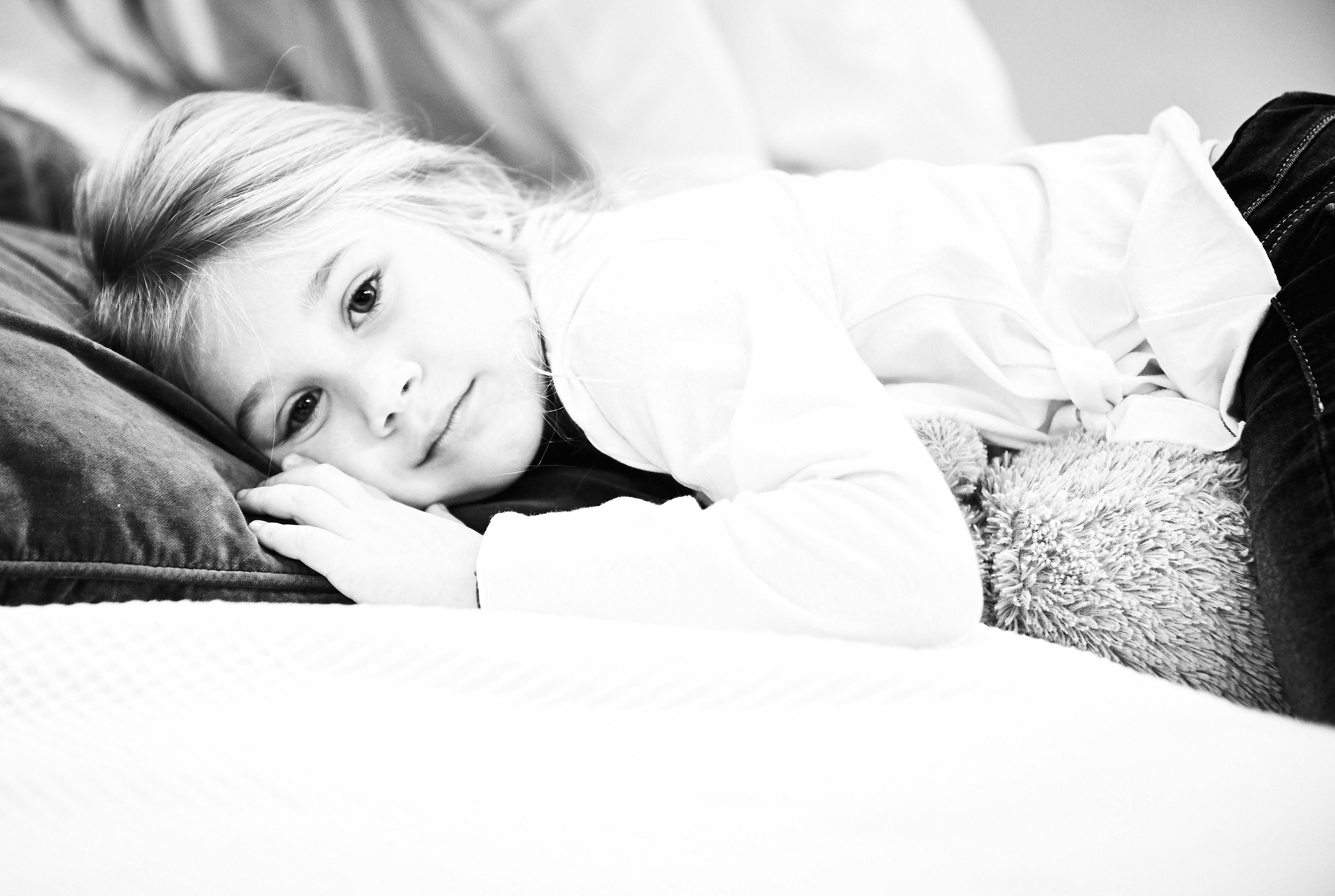 fotografia bambina in bianco e nero sdraiata su divano
